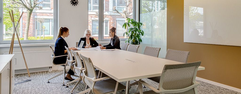 Three businesswomen sat around a large meeting table